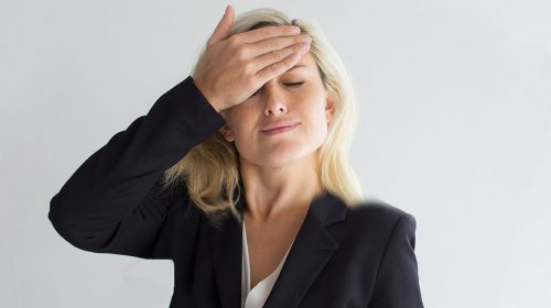 Studio portrait of forgetful young Caucasian businesswoman wearing costume slapping her forehead